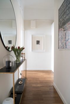 Elegant & narrow entryway with round mirror & console table