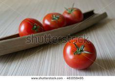 Stock Photo:     Ripe tomatoes on wood background     Image ID:461059495     Copyright: Alina Craita