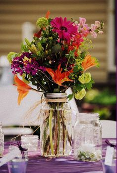 """Want floral centrepieces without spending a fortune? No problem - mason jar with grocery store flowers and twine! An easy and affordable """"wild flower"""" centre piece for a bride on a dime!"""