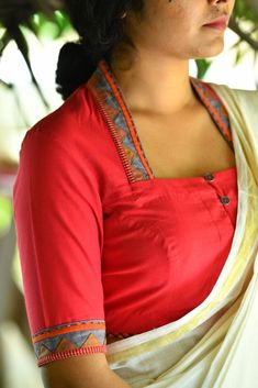 A simple bodice style blouse in dull red with a Theyyam appliqué border.This appliqué is an intricate combination of muted blue and checkered strips agai...
