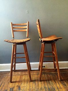 Vintage mid century high top kitchen bar swivel chairs. Wood slatted seats with black metal bracing fastened a top a wood frame . This pair is as