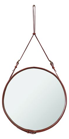 The Danish Gubi Adnet wall mirror with a tan leather strap.