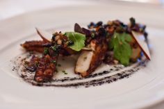 Charred octopus -blanketed in a heady fermented black bean and pear sauce, with an ink and miso vinaigrette and purple basil- Le Bernardin