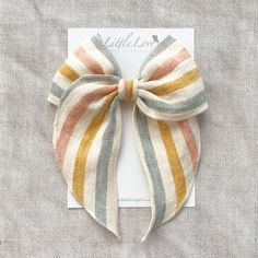 Rainbow stripe linen bow hair clip from Little Love accessories, stripe design linen bow in coral, yellow and blue, a perfect girls Summer Hair Bow Say hello to our rainbow inspired hair bow in beautiful striped linen. The rainbow has become a symbol of hope across the world, bringing joy through children's pictures on windows, so why not in a bow...Little Love style! Our Hair Bows come on a strong matching grosgrain covered double prong crocodile clip and can be worn in variety of… Fabric Hair Bows, Ribbon Hair Bows, Girl Hair Bows, Bow Hair Clips, Girls Bows, Bow Clip, Hair Bow Tutorial, Fabric Bow Tutorial, Baby Hair Accessories