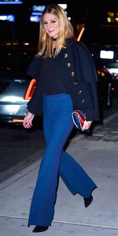 Palermo was sailor-chic for dinner in Manhattan, pairing a buttoned navy coat with ruffled sleeves with wide-leg trousers. She topped off the look with a graphic clutch and black booties.
