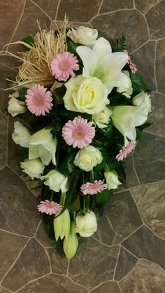 Funeral spray with roses, lilies and germinis.