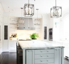 The White Kitchen. Nice lighting. Dramatic marble slab backsplash