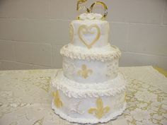3 tier cake for the 50th wedding anniversary - bottom tier vanilla, middle chocolate and top strawberry.  Covered in Vanilla buttercream icing and accents are fondant painted gold.