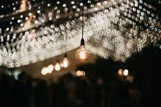 Vintage drop bulbs punctuate the ceiling, creating a warm glow. Wedding Film, Wedding Events, Marquee Wedding, Amazing Weddings, Vintage Lighting, Bulbs, Tent, Glow, Ceiling Lights