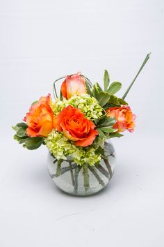 Orange Roses bubble between green hydrangea in this bright arrangement From Blossom Flower via @BloompopHQ
