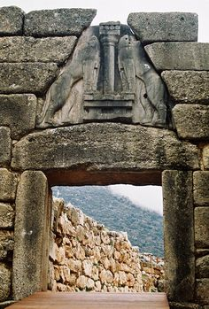 Lions Gate, 1300-1250 BCE, Mycenae Greece]  The Lion Gate consists of two monoliths surmounted by a triangular stone sculpture in which a central pillar of Minoan type is flanked heraldically by a pair of high relief lions.