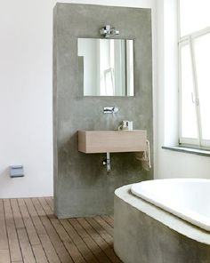 A concrete tub surround and wall, paired with a wood floor, in a bath spotted at Taverne Agency.