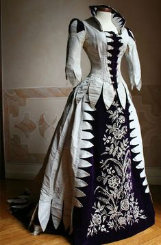 What a dress! I wonder how long it took to do that embroidery and to applique the triangle type pieces. Looks as if made by someone with more type than money!