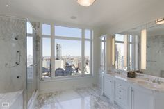 This NYC bathroom has marble floors, walls, and counters. It also has white cabinetry, a glass enclosed shower, linear light fixtures and a large picture window overlooking the city.