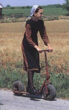 A young Amish girl travelling down the road on a hot summer day.