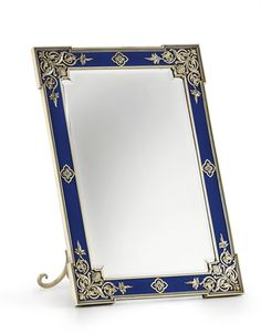 A Large Silver-Gilt and Guilloché Enamel Photograph Frame  Marked Fabergé, workmaster's mark of Victor Aarne, St. Petersburg, 1896-1904, scratched inventory number 7527 Rectangular with outset corners, enameled in translucent royal blue over a wavy guilloché ground within a beaded border, applied with cast and chased openwork foliate motifs in the Old Russian style, with stepped bezel now enclosing a mirror, with scroll strut, in a fitted Wartski case, marked on lower rim and strut.