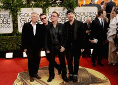 Adam Clayton, Larry Mullen Jr., Bono, and The Edge of U2 attend the 71st Annual Golden Globe Awards.  Photo by Jason Merritt/Getty Images