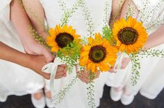 Flower girls in white dresses each hold single sunflower.
