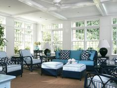 This sunroom with navy wicker furniture, blue-and-white striped cushions and sisal carpeting has a breezy, beachy feel. A coffered ceiling dresses up the look and includes a useful ceiling fan for hot summer days.