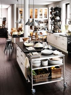The white cabinets with black counter tops with stainless steel appliance and light fixture is a good combo.