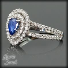 LS1298 She will feel like a queen when she puts on this regal pear shaped Blue Sapphire and Diamond Halo Engagement Ring! The sapphire in this