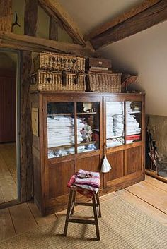 ROQUELIN, LOIRE VALLEY, FRANCE: SEWING ROOM; WOODEN BEAMS AND WOODEN FLOORING, VINTAGE GLASS CABINET HOLDS COLLECTIONS OF VINTAGE LINENS, WITH MORE IN BASKETS ON TOP