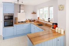 This open plan kitchen features Shaker style cabinetry painted in Farrow & Ball's Lulworth Blue, alongside full stave Prime Oak worktops and matching upstands for a modern, elegant look.  Effective use of storage comes in the form of a variety of different cabinet and drawer sizes finished with cornices, tongue and groove panelling and other refined details. http://www.solidwoodkitchencabinets.co.uk/gbu0-display/gallery.html