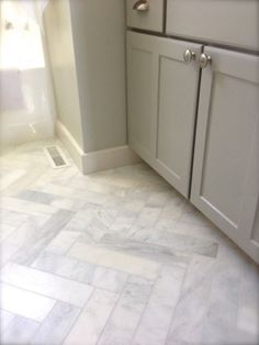 It's a lot of cutting, but a 12x12 inexpensive Home Depot Carrera tile cut to 3x12 and do herringbone floor would be fab.