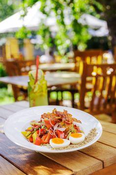 Salată de legume proaspete și bacon crocant. Conține roșii, castraveți, ardei, ceapă roșie, dressing de casă, bacon și ou.