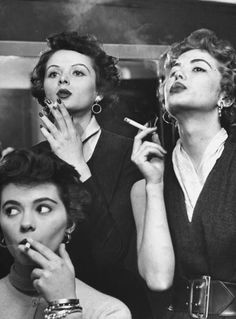 Models exhaling elegantly, learning proper cigarette smoking technique in practice for TV ad, circa 1953.
