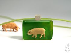 Chic pig – funny pig pendant with a light pink pigs in front of a green background made of resin as a lucky charm  ///// © Isabell Kiefhaber www.geschmeideunterteck.de