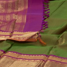 "The ""Green"" body of this Kanjivaram Silk Sari from Parisera is woven with zari peacock motifs all over the body that is set off by a zari border on either side. Elephants, Horses, Peacocks and Paisleys in zari adorn the magenta pallu. The border is repeated on the magenta blouse that completes the sari."