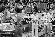 Nadia Comaneci, right, watches raging controversy in Moscow on Thursday, July 24, 1980, which broke out among judges and officials following the final performance of Nadia Comaneci of Romania on the balance beam. The Romanians objected to the decision by four Eastern European referees to award Comaneci only 9.85 for the beam routine. (AP Photo)