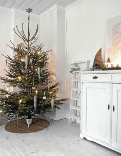 Scandanavian Christmas Style Concepts - Neutral color palette of whites and silvers - natural greenery and pine cones with sparse ornaments - wool blankets and animal skins add warmth to modern furnishings - Candle, candles, candles