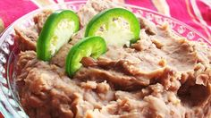 Flavorful refried beans seasoned with garlic, jalapeno, and cumin are simple to make when cooked in a slow cooker.