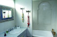 La zona de la bañadera agrega aires marroquíes a la ambientación, con un nicho trabajado a modo de pórtico oriental y un grupo de perfumeros en la misma tónica. Sobre el muro que la separa del área de muebles se colgaron dos percheros de hierro con forma de mariposa que se usan para collares.
