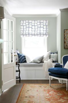 ♥Blue and white pillows and a custom roman shade (made with Christopher Farr fabric) reinvented an entryway as a reading nook in this Massachusetts home.