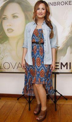 Demi Lovato escolheu um look boho para a coletiva de imprensa no Rio: vestido mullet estampado, camisa jeans, sapatos pesados e brincos de pena!