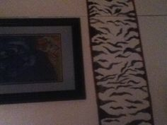 Siberian tiger striped border-  Painted my brown panel walls w/ Kikz2, 3 coats, then painted w/ white paint. I hand painted tiger stripes for my border w/ black paint. I bought dollar tree bamboo mats, cut them apart and hot glued them to my border.   ~Brenda Madden's Worx of Art~