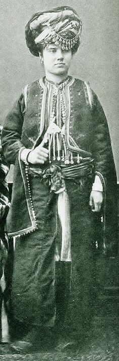 The festive/ceremonial costume of a Kurdish townswoman from Harput.  Late-Ottoman, ca. 1870.   The impressive headgear (called 'hotoz') implies many scarves (some of light colours, some dark), which are braided by each other on top of a small cap.  A double chain with dangles is fixed to the 'hotoz' by means of two golden head pins.  Picture from 'Les Costumes Populaires de la Turquie'- Osman Hamdi Bey, 1873. (Erfgoedbibliotheek, Antwerpen).