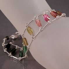 A gorgeous gemstone bracelet featuring multi-colored tourmaline in a rainbow ladder with silver bar chain.