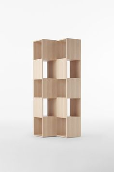 FOLD by nendo (JP) for Conde House in 2013.  A shelving unit made of interlocking wooden boards oriented to different angles to the left and right. Thanks to the superior craftsmanship of Conde House, a wood furniture manufacturer in Asahikawa in northern Japan, the joints appear seamless, as though single boards have been bent and interwoven like paper chains or a woven textile. It's virtually impossible to know, looking at the shelves, how the parts are connected.