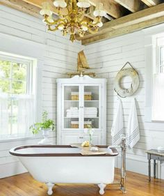 Pretty vintage bathroom with old, white-washed shiplap, and a few nautical touches.