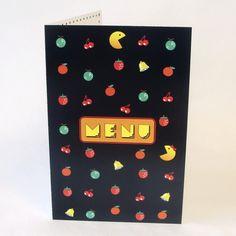 Assorti au faire-part sur le thème Jeux vidéo. Carte double rectangulaire. fond noir, décor fruits et cloches stylisés. Pour refaire le plein d'énergie quoi de mieux qu'un bon banquet de fête ! Pour poursuivre le jeu jusqu'au dernier niveau (le bal !) les Pacman amoureux croquent tout !