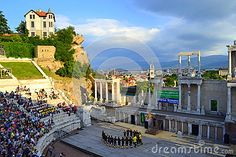 Bulgarian folk group dancing at ancient Roman amphitheater  stage during the annual folklore festival and scenic view of  Plovdiv city ,Bulgaria.