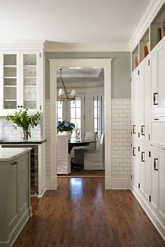 Beautiful kitchen design with white subway tiled backsplash and contrasting grout. Fabulous wall of white cabinetry with bookshelves above for cookbook storage.