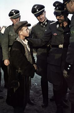 Reichsführer-SS Heinrich Himmler talks through an interpreter to a local boy during an inspection tour of Belarus. To Himmler's right is his chief adjutant Karl Wolf. The year is 1942.