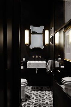 This Small Art Deco Downstairs Loo in bathroom design ideas has black walls and a white ceramic bathroom site with monochrome floor tiles and art deco lighting