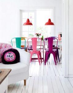 Cozinha branca com cadeiras e acessórios cheios de cor