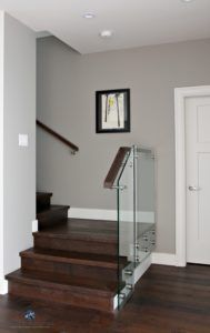 Sherwin Williams Dorian Gray in contemporary stairwell with glass and dark wood. Kylie M Interiors Decorating, Design and Online Color Consulting Services
